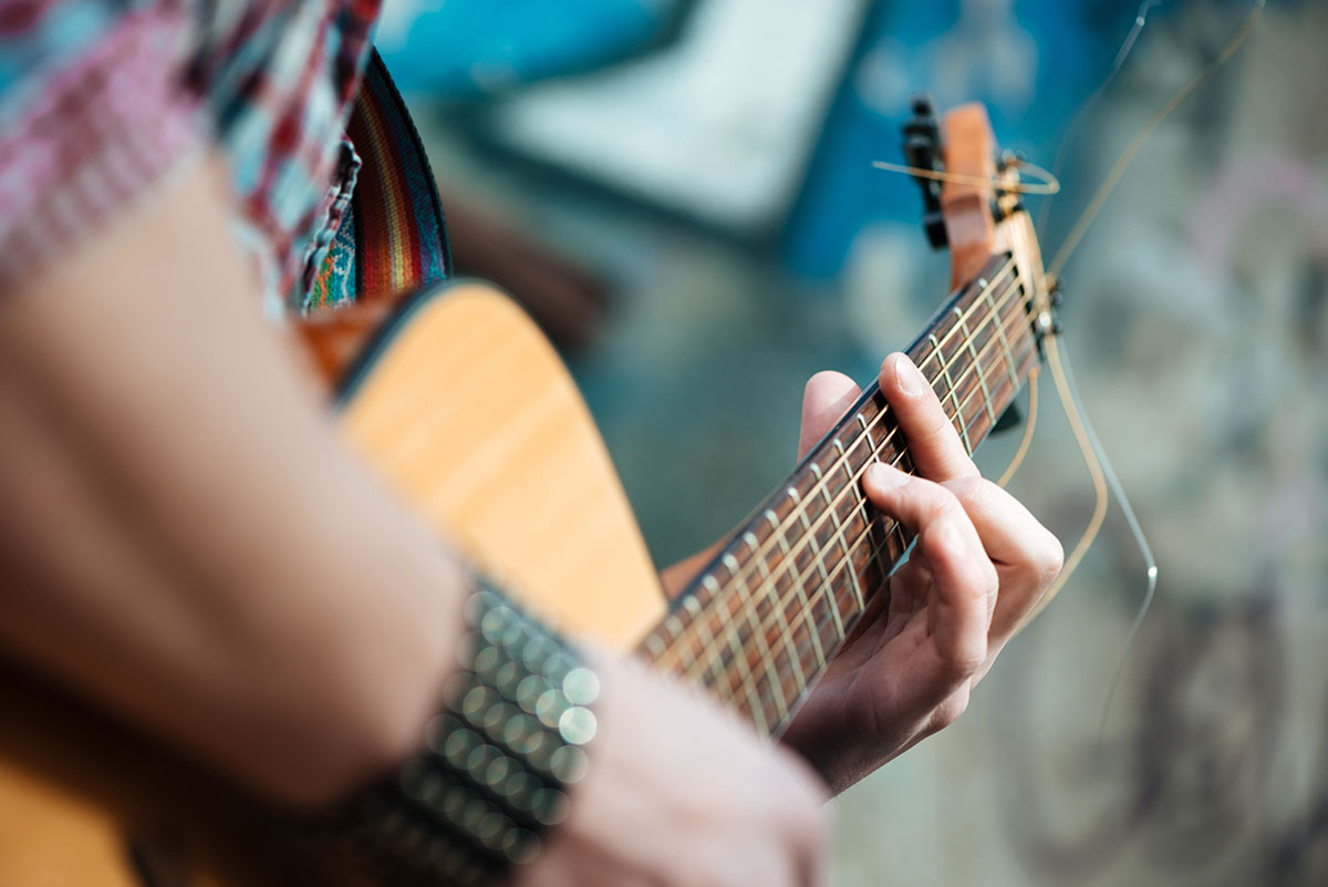 male-hands-playing-on-guitar-outdoors-PVCMQP3