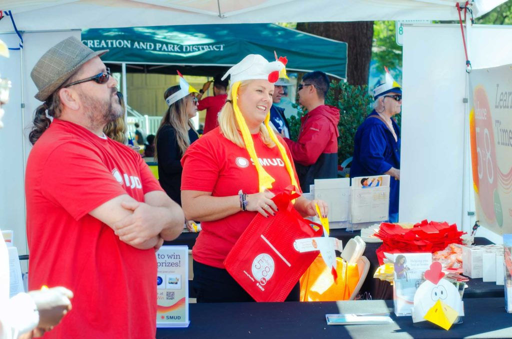 people in red shirts and chicken hats at the fair oaks chicken festival in fair oaks village