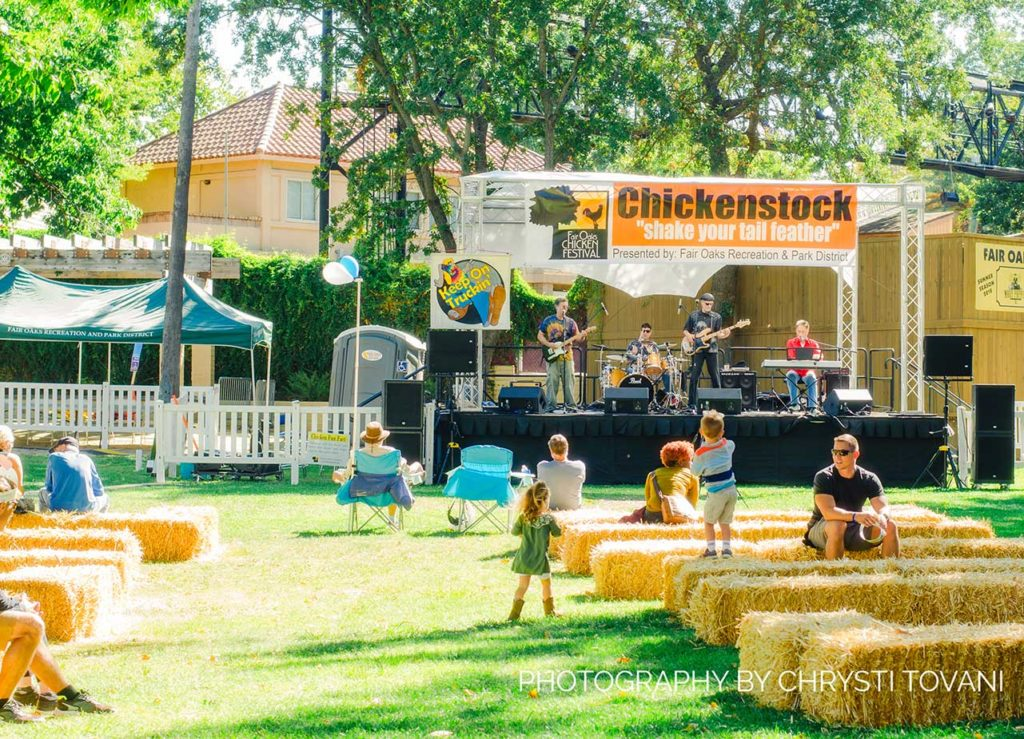 live band playing on the main stage at the fair oaks chicken festival people sitting on bales of hay in the park
