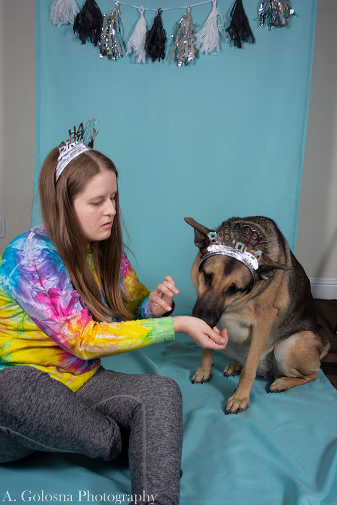 young woman wearing a tierra with her dog also wearing a tierra and getting a pet portrait