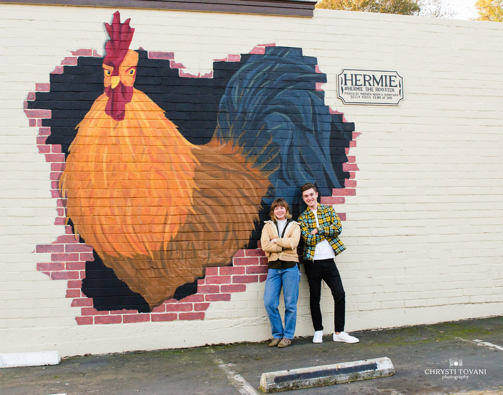 Matthew and Alayna pose in front of their mural of hermie the rooster in fair oaks village