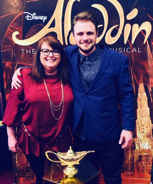 two people standing in front of the Aladdin backdrop at the Sacramento Community Center Theater